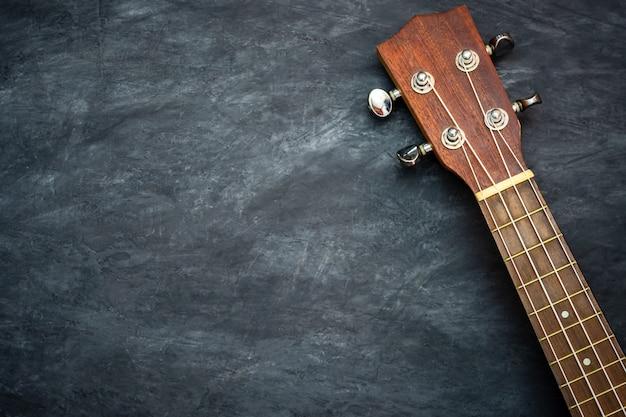 Укулеле на черном цементе. концепция гавайских музыкальных инструментов и меломанов. Premium Фотографии
