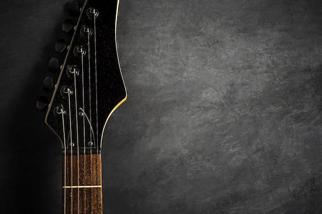 黒いセメントの床に黒いエレキギターのヘッドストック。テキストのトップビューとコピースペース。ロックミュージック。 Premium写真
