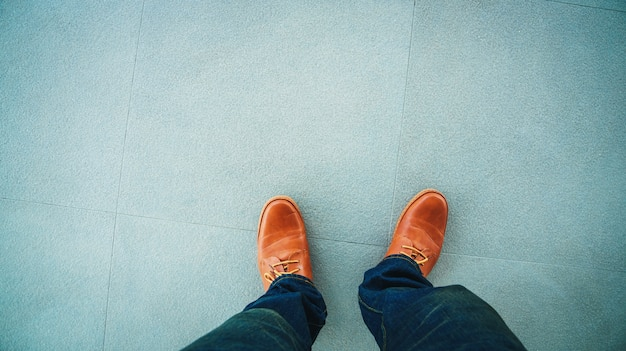 石の床のタイルの背景に立っている革靴のトップビュー Premium写真