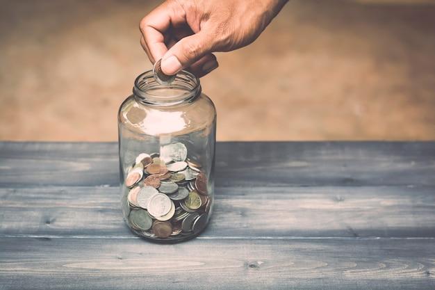手は貯金のためにガラス瓶にお金を落とす Premium写真