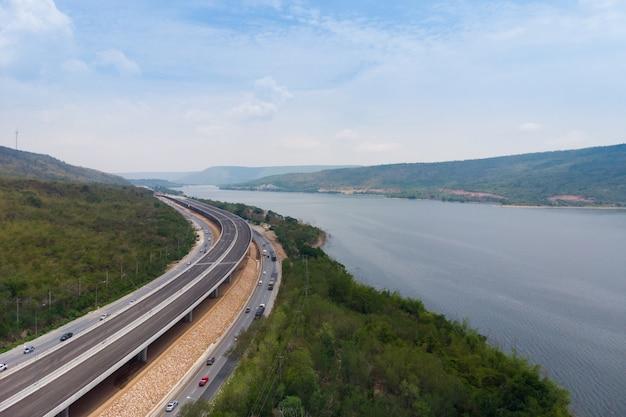 大きな自然の川の近くの建設中の高速道路通行料の下のドローンショット空撮風景 Premium写真