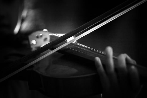 暗いトーンと照明効果のバイオリンオーケストラの楽器を演奏する少女のクローズアップショット Premium写真