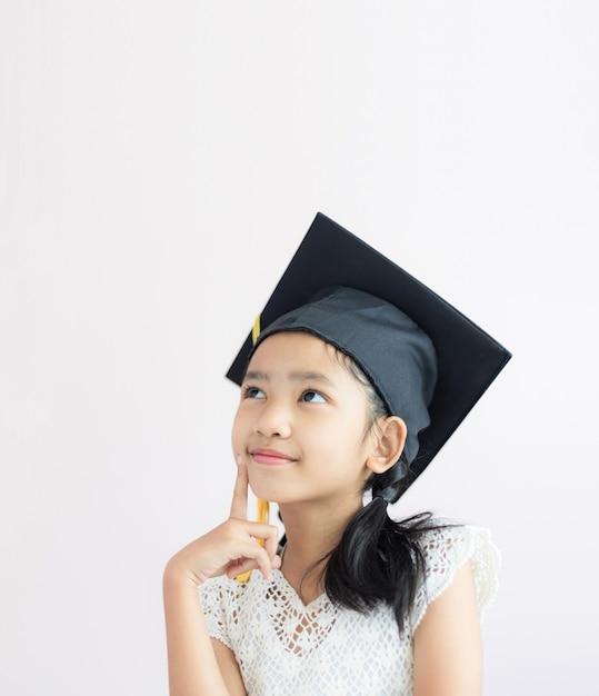 アジアの少女の肖像画は大学院の帽子と幸せと笑顔を着ています。 Premium写真