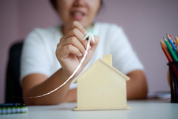 鉛筆を使用して幸せなアジアの女性は、家を買うためのお金を節約木造貯金箱メタファーと上矢印図形を描く Premium写真