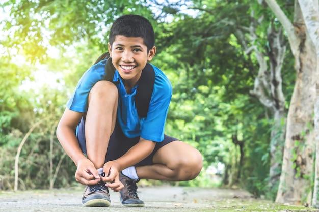 Азиатский мальчик студент носить обувь ходить в школу Premium Фотографии