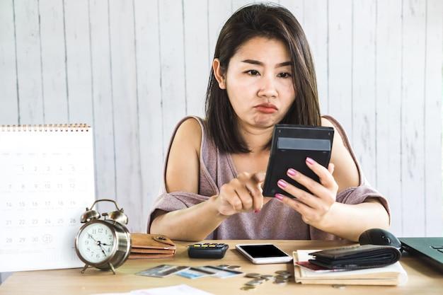 アジアの女性が電卓で費用を数える Premium写真