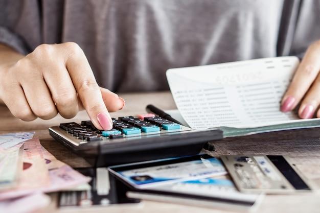 女性の手が貯蓄口座にお金を計算します。 Premium写真