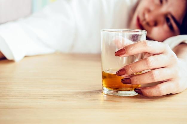 アルコールのガラスを飲む女性の手をストレスします。 Premium写真