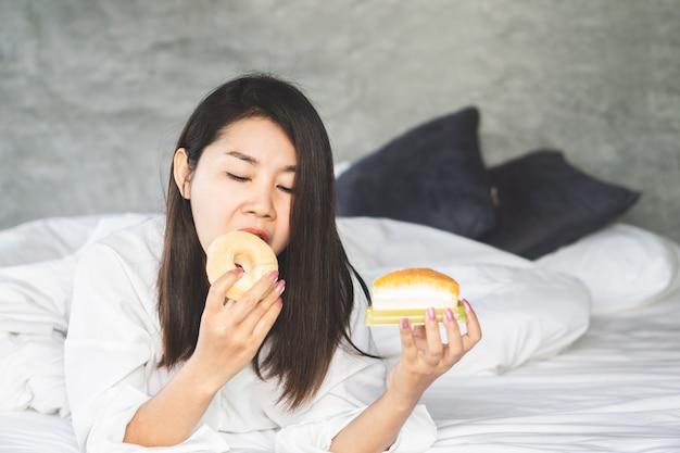 不健康なアジア女性のベッドの上でデザートを楽しむ Premium写真