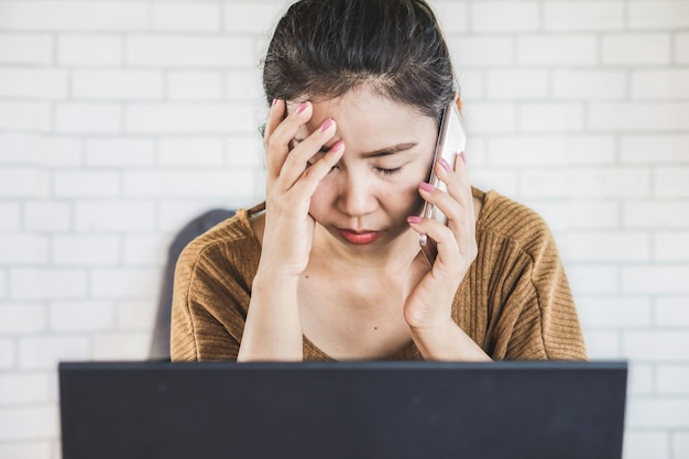 職場で電話で話している悲しいアジア女性 Premium写真