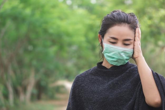 頭痛を持つマスクを着て病気のアジアの女性 Premium写真
