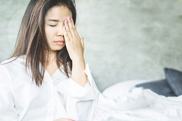 Азиатская женщина имеет головную боль и боль в глазах от мигрени Premium Фотографии