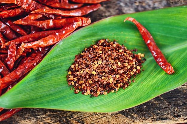 赤い乾燥唐辛子と緑の葉のクローズアップのチリパウダー Premium写真