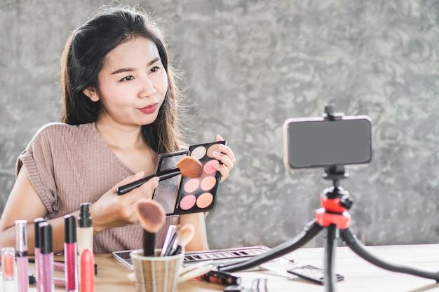 アジアの美容ブロガーがスマートフォンでライブ Premium写真