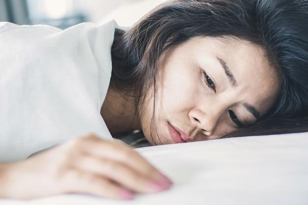 Бессонная азиатская женщина лежа на кровати Premium Фотографии