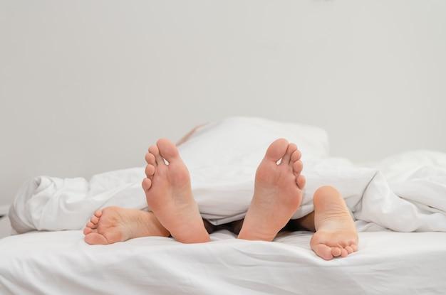 Ноги влюбленной пары на кровати занимаются сексом под белыми одеялами Premium Фотографии
