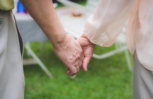 年配のカップルが自宅の庭で一緒に手を繋いでいます。 Premium写真
