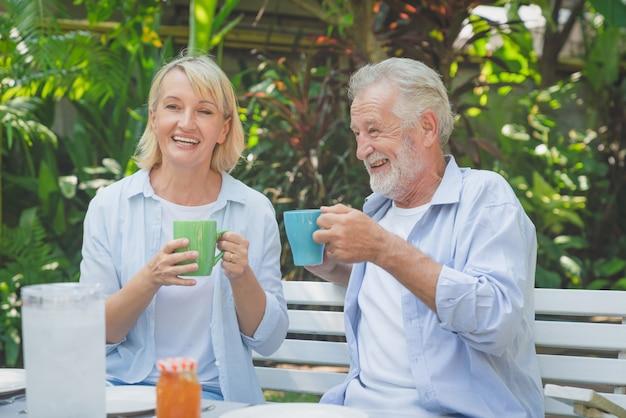 家の庭で朝のコーヒーを飲みながらリラックスした幸せな先輩カップル Premium写真