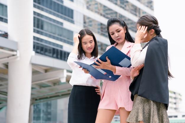 Руководитель бизнес-леди ищет ошибку финансового отчета коллег во время ходьбы вернуться к работе в офисе Premium Фотографии