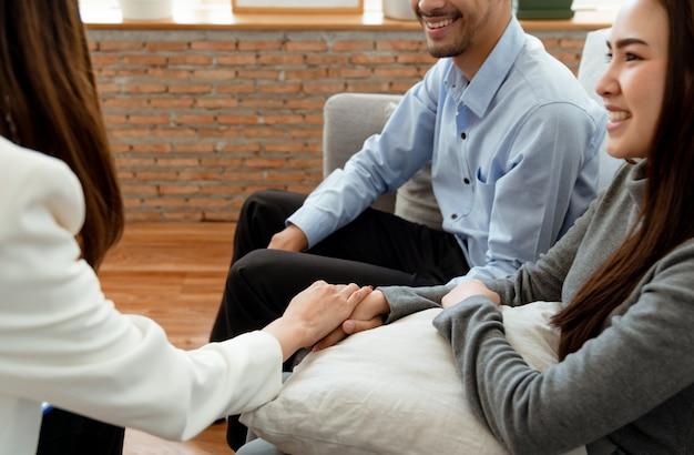 女性精神科医は、問題を抱えて精神科医からアドバイスを受けた後、彼らの良好な関係を祝福するために、カップルの笑顔で手をつないでいます。 Premium写真
