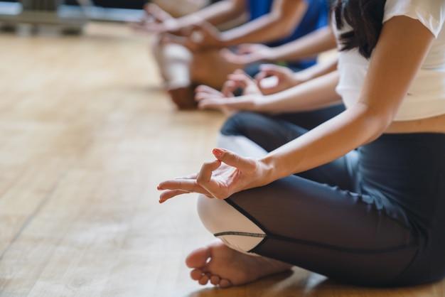 Крупным планом женщина руками практикует йогу и медитацию в позе лотоса в фитнес-клубе Premium Фотографии
