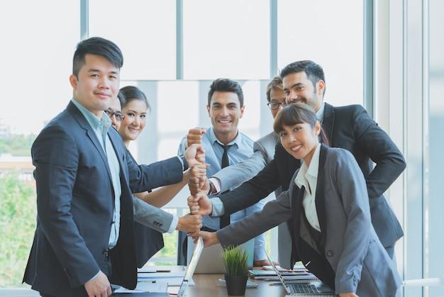 ビジネスチームの握りこぶしのグループは、オフィスで成功するために準備ができて一緒にスタックします。 Premium写真
