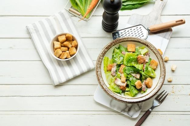 木製の白いテーブルの上皿に新鮮なシーザーサラダ。健康食品、トップビュー Premium写真