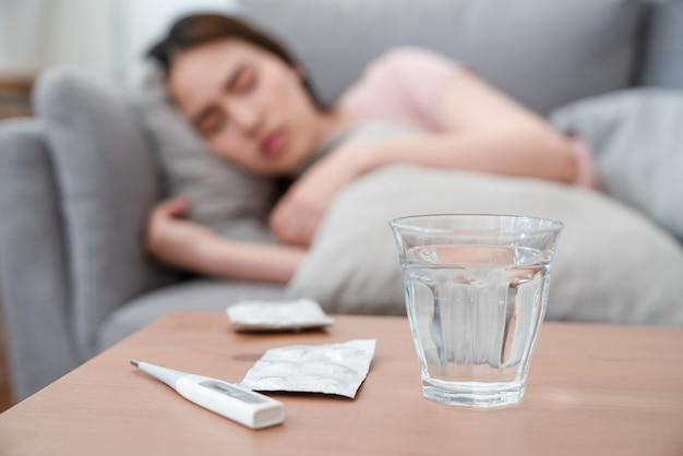 水のガラス、薬のパックと薬を服用後ソファ枕に横たわっている病気のアジア女性とテーブルの上のデジタル温度計 Premium写真