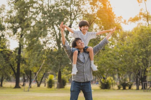Счастливый и весёлый азиатский папа катает сына на своих плечах, словно летит в парке Premium Фотографии