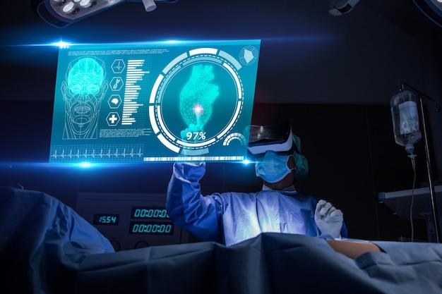 病院の手術室における仮想現実を持つ医師。技術的なデジタル未来的仮想インターフェースに関する患者の心臓検査結果と解剖学の分析外科医 Premium写真