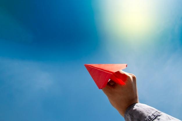 赤い紙飛行機を持っている人間の手 Premium写真