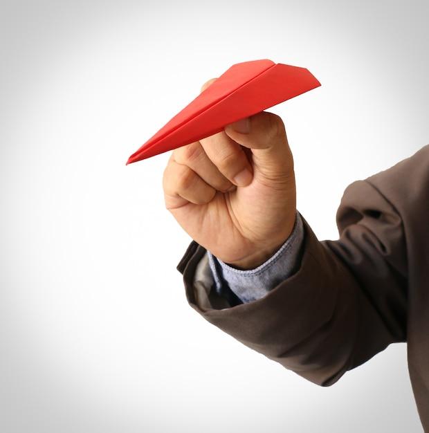 Человеческая рука держит красный бумажный самолетик Premium Фотографии