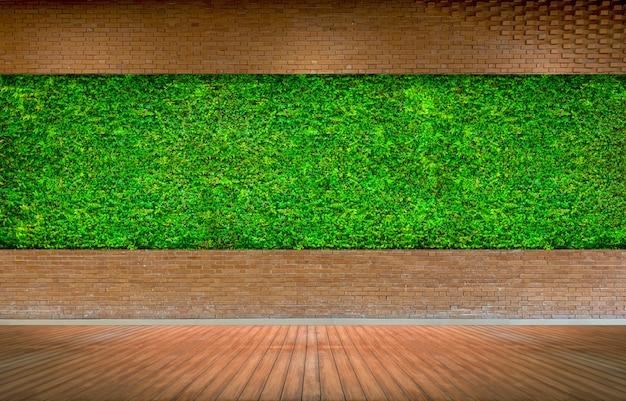 新鮮な緑の芝生の背景を持つ赤レンガの壁 Premium写真