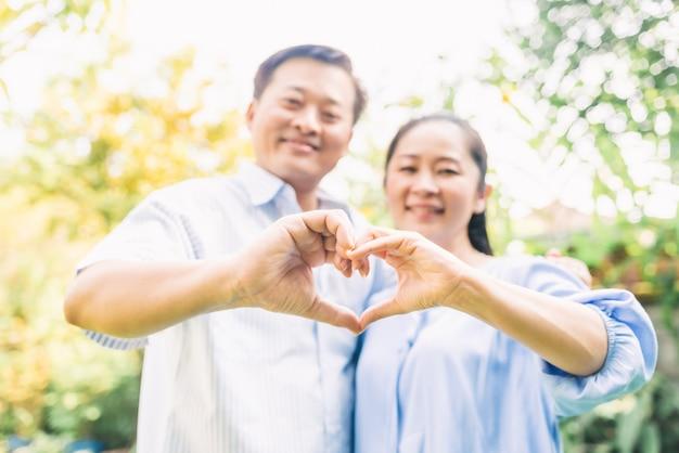 ハート形のジェスチャーをしている年配のカップル Premium写真