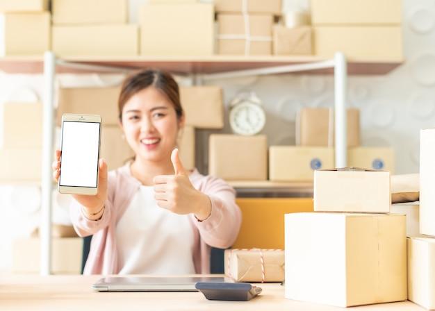 アジア人の女性が親指でスマートフォンを表示 Premium写真