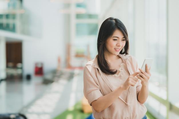 近代的なオフィスでスマートフォンを使用しながら笑顔の女性 Premium写真