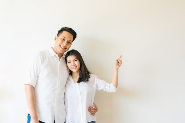 Азиатская пара счастлива, указывая пальцем на пустой копией пространства на стене Premium Фотографии
