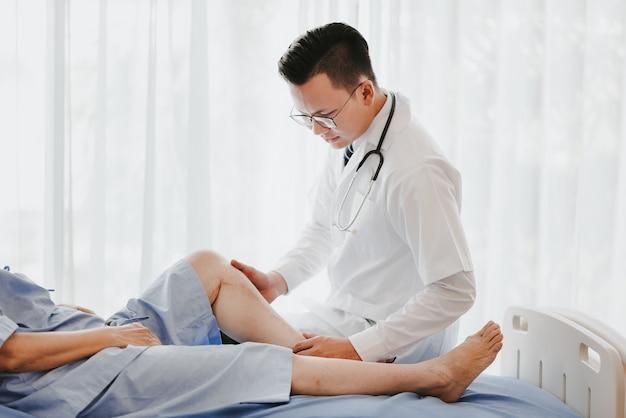 病院のベッドで患者の膝を調べる医師 Premium写真