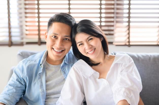 自宅のソファーでリラックスした笑みを浮かべて愛のアジアカップル Premium写真