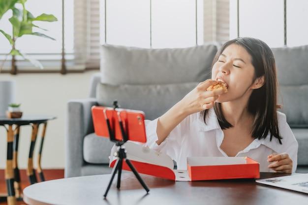 新しいコンテンツビデオを作成しながらピザを食べる女性フードブロガー Premium写真