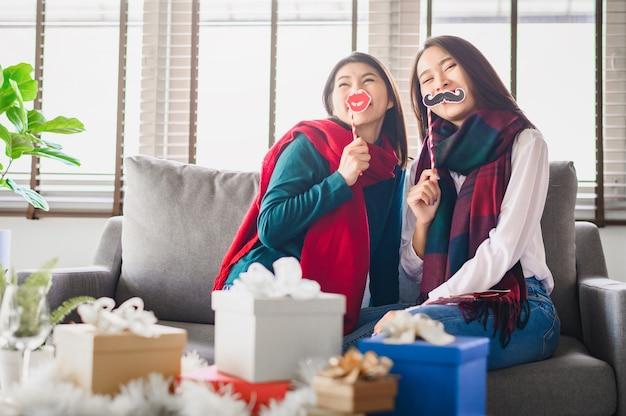 Две азиатские женщины лучшие друзья веселятся вместе в течение нового года Premium Фотографии