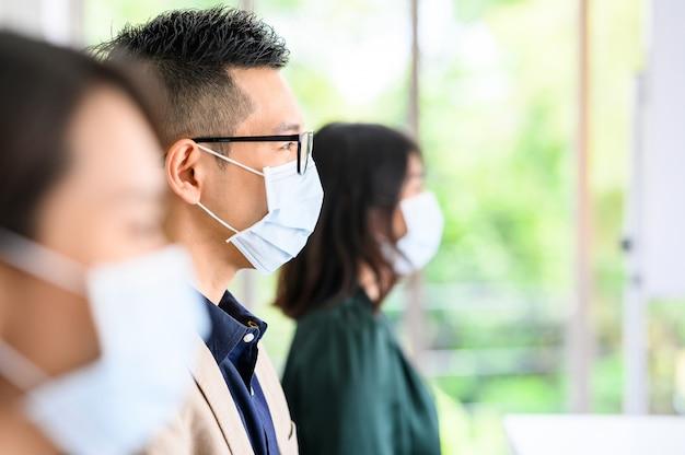 アジアの人々の列は安全のために防護マスクを着用しています Premium写真