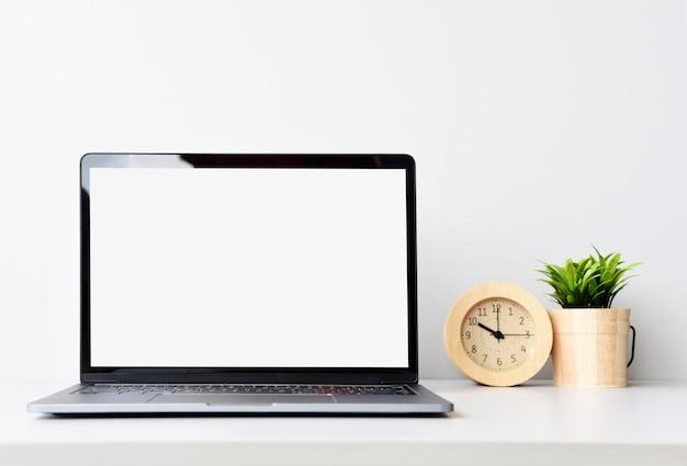 Работа с ноутбуком на столе в белой комнате Premium Фотографии