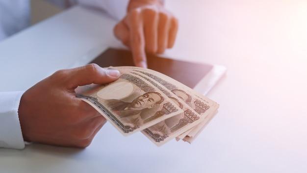 手、円、投資、成功と収益性の高いビジネスコンセプトのお金のあるビジネスマン。 Premium写真