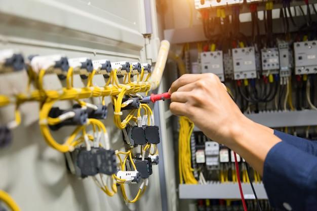 電気技師はコントロールパネルで現在の電気をテストする手。 Premium写真