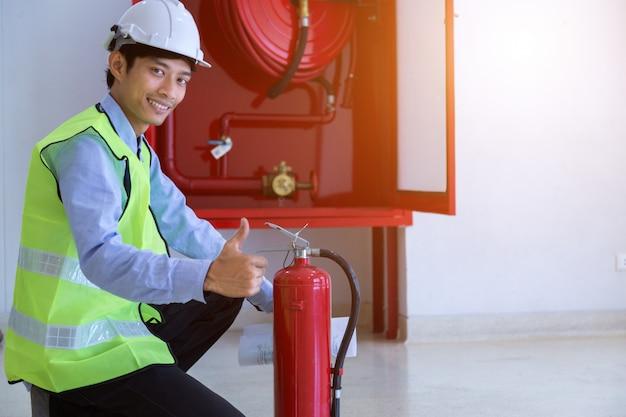 Инженер осмотр огнетушитель и пожарный шланг. Premium Фотографии
