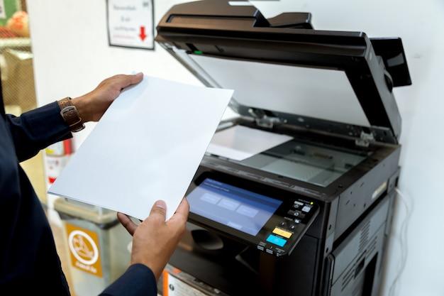 Деловой человек ручная кнопка на панели принтера, сканер принтера лазерная офисная копировальная машина начала концепции. Premium Фотографии
