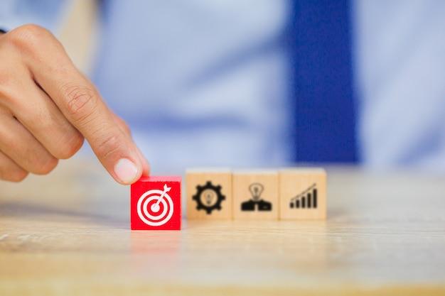 ビジネスマンの手がターゲットの成功の概念を上にウッドキューブブロックを置くこと。 Premium写真
