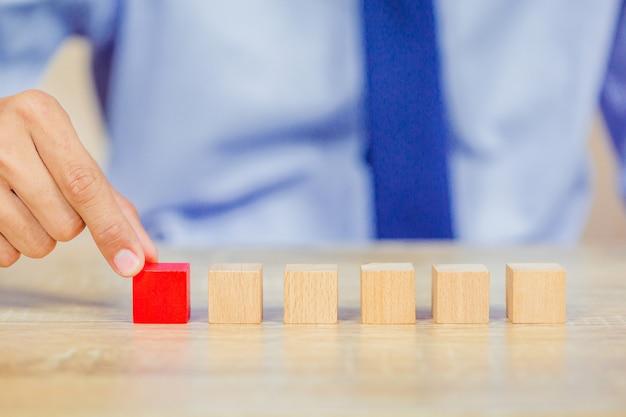 Руки бизнесменов, укладывая деревянные блоки в шаги. Premium Фотографии