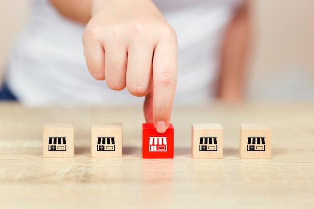 Рука женщины выбирает деревянный блог с маркетингом франшизы. Premium Фотографии